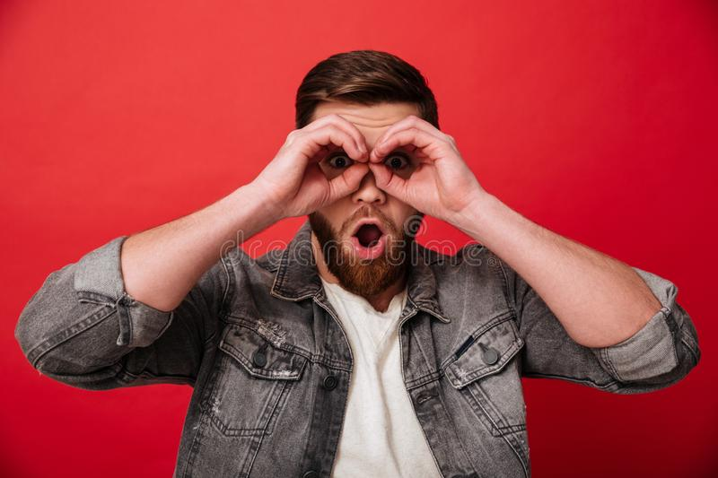 Portrait of joyful guy 30s in jeans jacket having fun and looking on camera through holes like binoculars, isolated over red back. Portrait of joyful guy 30s in royalty free stock photo