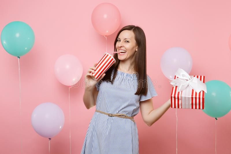 Portrait of joyful laughing woman in blue dress holding red box with gift present drinking soda or cola from plastic cup. On pastel pink background with royalty free stock images