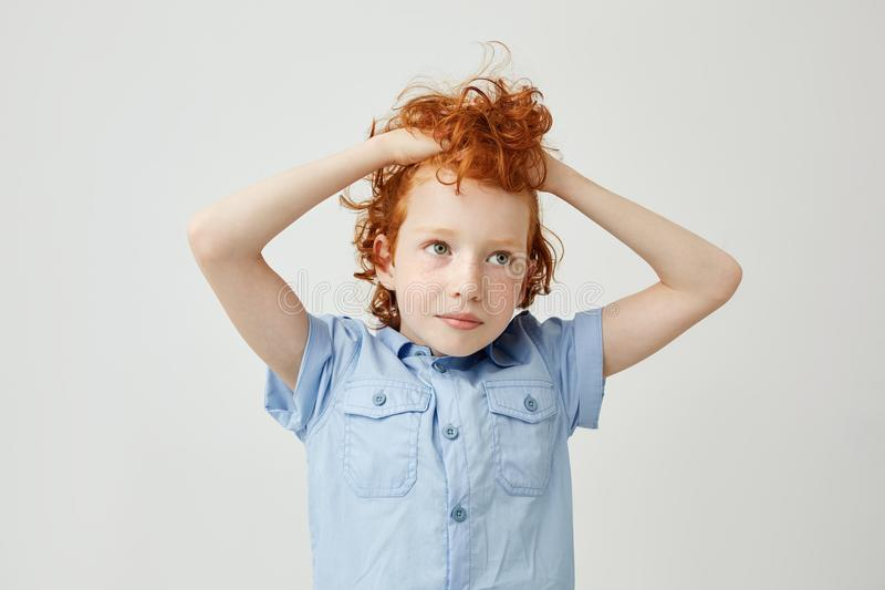 Portrait of joyful little ginger boy with wavy hair and freckles holding hair in hands, looking aside with tired and royalty free stock photos
