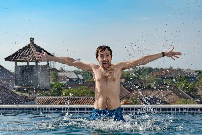 Portrait of joyful slender man with chest hair, emerges from pool, water splashes, shows tongue and hands up, on hotel roof. royalty free stock images