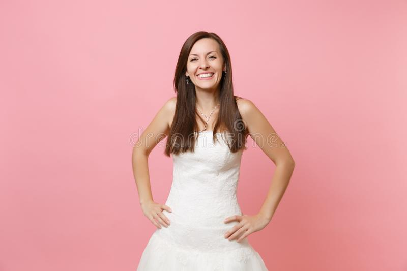 Portrait of joyful smiling bride woman in beautiful white wedding lace dress standing with arms akimbo isolated on pink royalty free stock photography