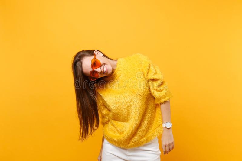Portrait of joyful smiling funny young woman in fur sweater, white pants and heart orange eyeglasses isolated on bright royalty free stock photos