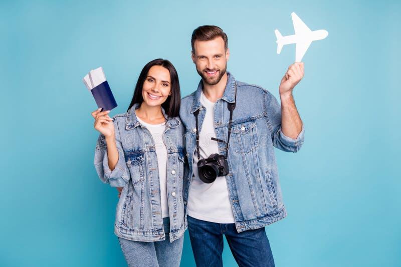 Portrait of joyful sweethearts holding passport papercard plane smiling hugging embracing wearing denim jeans  stock images