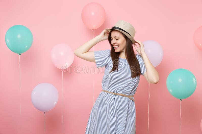 Portrait of joyful tender young woman with closed eyes in straw summer hat and blue dress on pastel pink background with royalty free stock photography