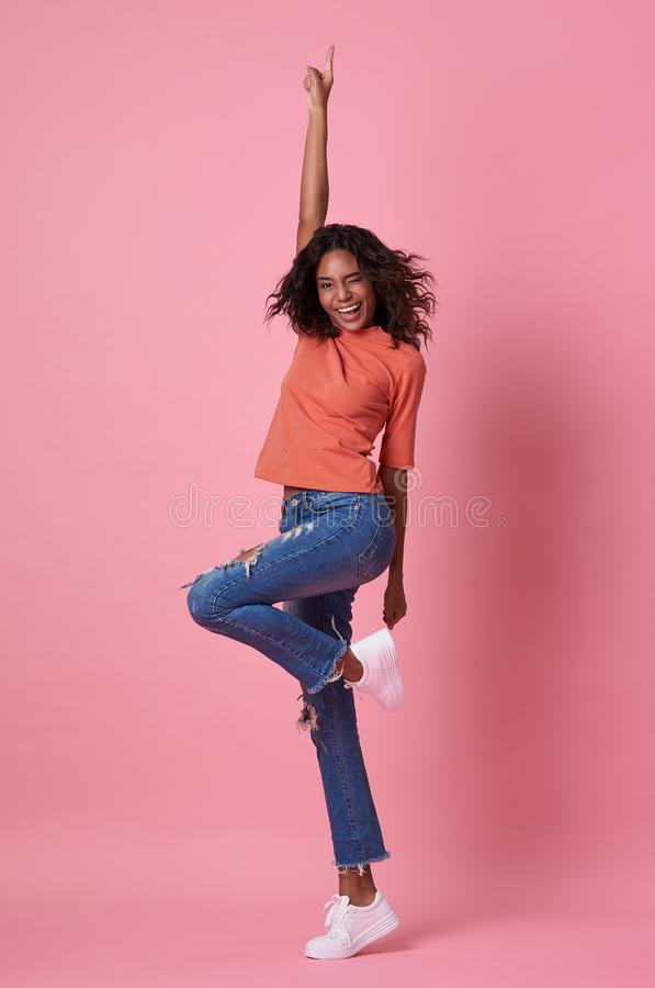 Portrait of a joyful young african woman in orange shirt jumping and celebrating over pink background.  royalty free stock photo