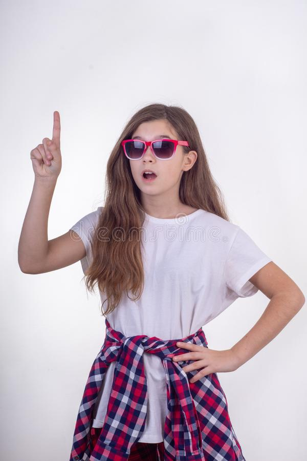 Portrait of joyful young girl with sunglasses posing and pointing finger at free space for advertisement. White stock images