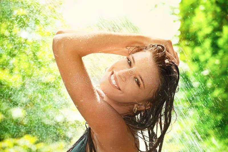 Summer rain. Portrait of joyful young woman under summer rain royalty free stock images