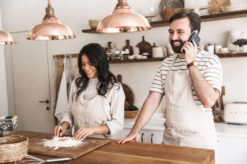 Portrait of joyous couple using smartphone while cooking together in kitchen at home royalty free stock images
