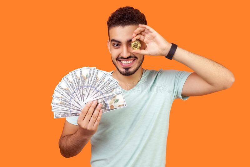 Portrait of joyous rich brunette man holding dollars and covering one eye with golden bitcoin. isolated on orange background stock photography