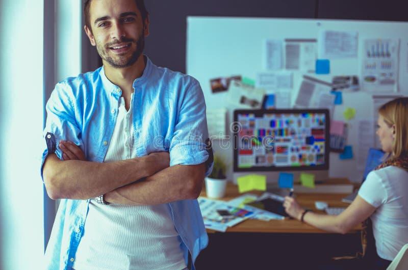 Portrait junger Designer vor Laptop und Computer beim Arbeiten. Assistentin, die ihr Handy im Hintergrund benutzt lizenzfreie stockfotos
