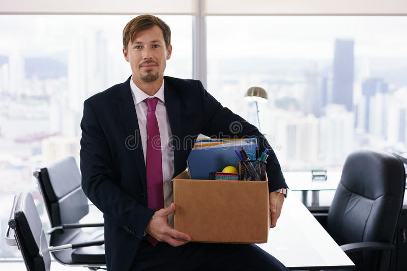 Portrait Just Hired Business Man With Crate Box Smiling. Businessman recently hired for corporate job moves into his new executive office with a view of the city royalty free stock image