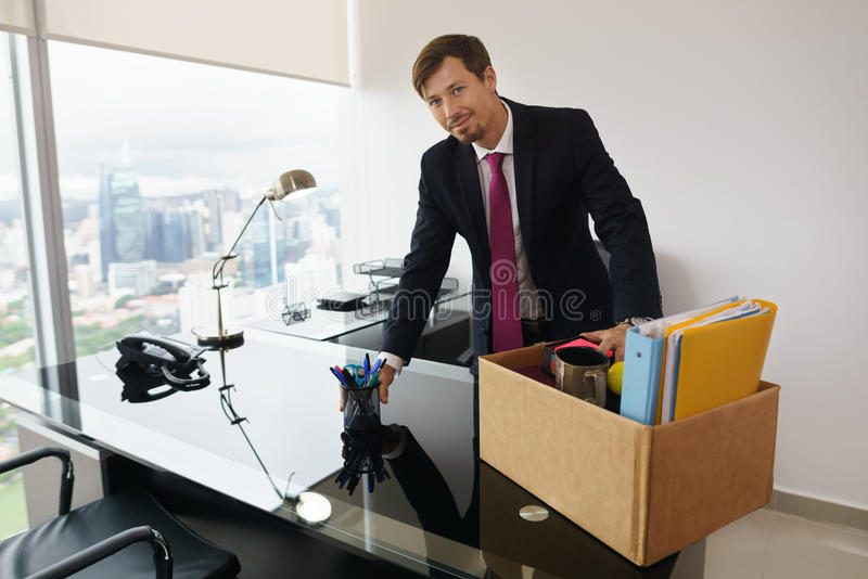 Portrait Just Hired Business Man In New Office Smiles At Camera. Businessman recently hired for corporate job moves into his new executive office with a view of stock photography