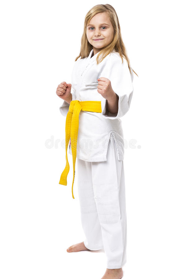 Portrait of a karate girl in kimono with yellow belt ready to fight stock image