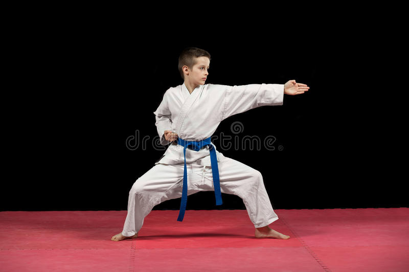 Portrait of a karate kid in kimono ready to fight isolated on black background royalty free stock photo