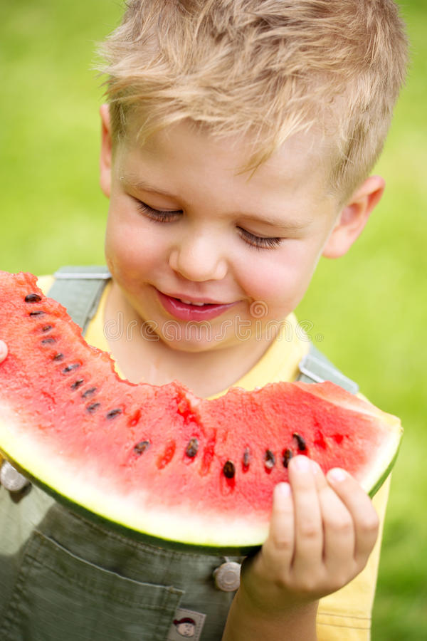 Portrait of a kid eating a slice of watermelon royalty free stock photos