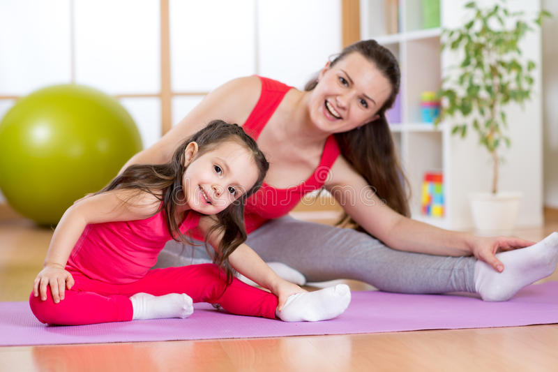 Portrait of kid and mother doing physical exercise at home. Portrait of kid girl and her mother doing gym exercise at home royalty free stock photography