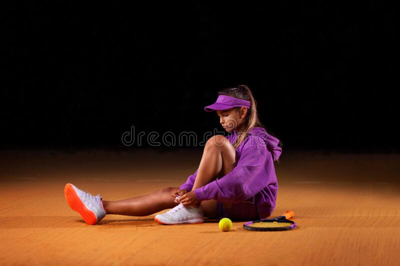Portrait of kid - tennis player. Beautiful girl athlete with racket in pink sporswear and hat on tennis court. Fashion royalty free stock photography