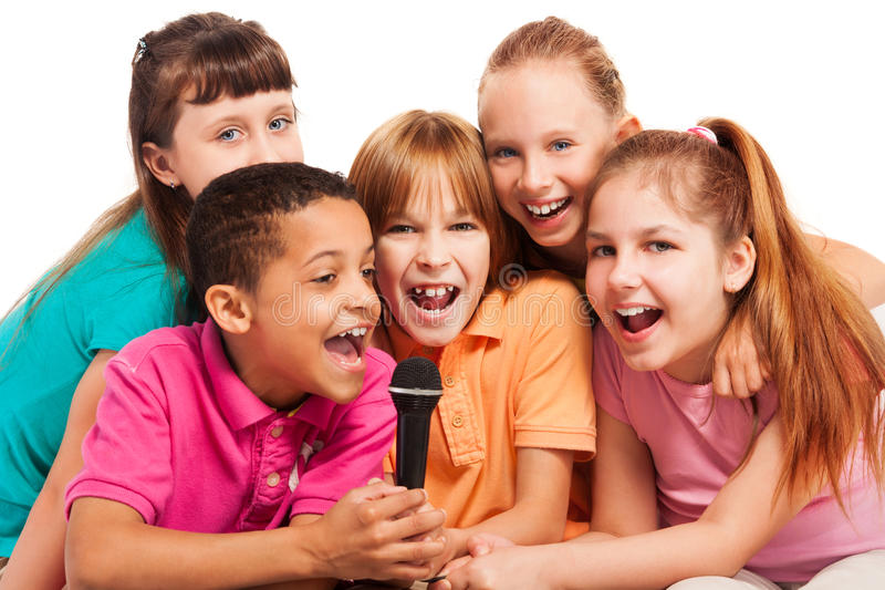 Portrait of kids singing together. Close-up of a group of happy exited diversity looking kids, boys and girls, singing together sitting on the coach in living stock photography