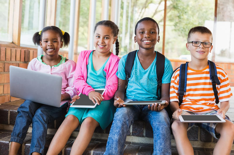 Portrait of kids using a laptop and digital tablet on stairs royalty free stock photography