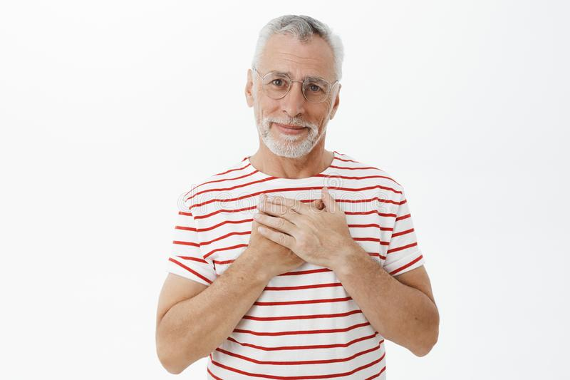 Portrait of kind and tender charming mature grandfather with grey hair and beard in bright striped t-shirt pressing stock image