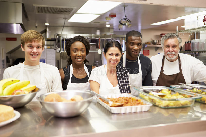 Portrait Of Kitchen Staff In Homeless Shelter. Behind Counter Smiling