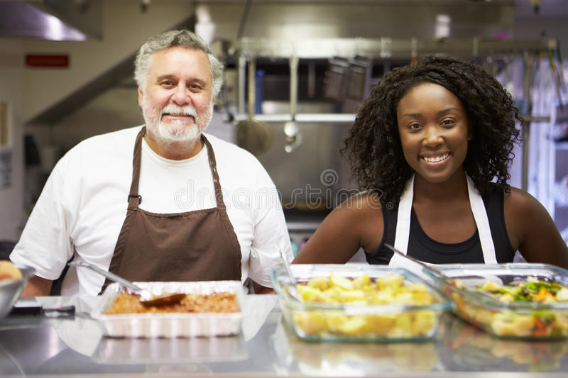 Portrait Of Kitchen Staff In Homeless Shelter. Smiling At Camera stock images