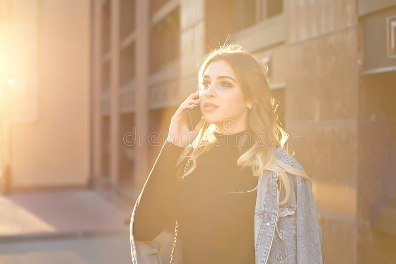 Portrait ?l?gant ?motif d'une jeune femme blonde sur un plan rapproch? de fond de paysage urbain dans le coucher de soleil photographie stock