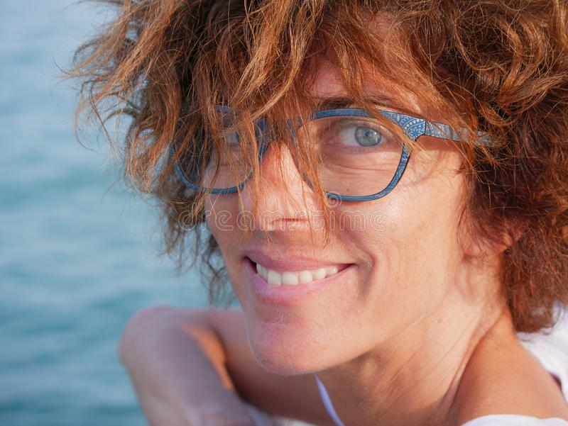 Portrait lady with blue eyes and glasses at sea. Smiling woman on cruise vacation, real people traveling, outdoors natural stock photos