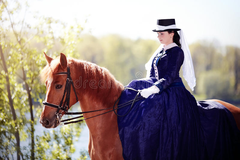 Portrait of the lady on a red horse. Lady on a horse. The lady on riding walk. Portrait of the horsewoman. The woman astride a horse. The aristocrat on riding royalty free stock images