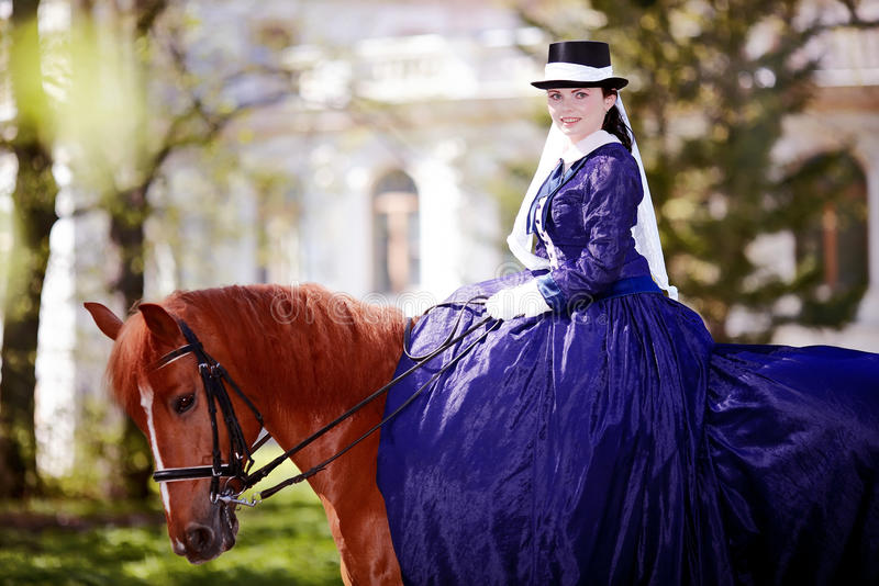 Portrait of the lady on a red horse. Lady on a horse. The lady on riding walk. Portrait of the horsewoman. The woman astride a horse. The aristocrat on riding royalty free stock photo