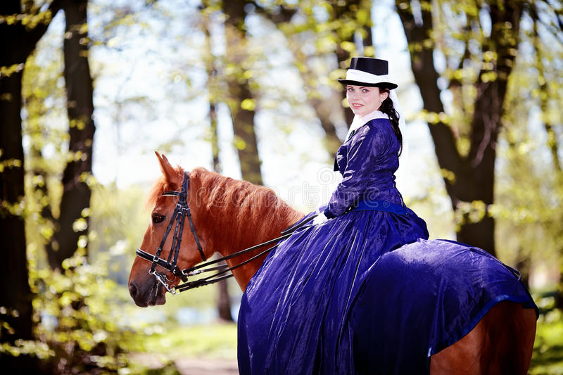 Portrait of the lady on a red horse. Lady on a horse. The lady on riding walk. Portrait of the horsewoman. The woman astride a horse. The aristocrat on riding stock photo