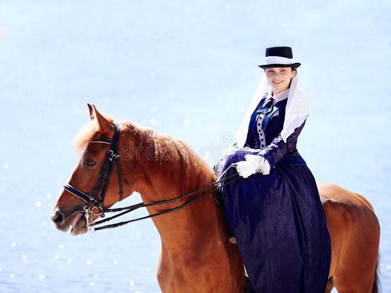 Portrait of the lady on a red horse. Lady on a horse. The lady on riding walk. Portrait of the horsewoman. The woman astride a horse. The aristocrat on riding stock image
