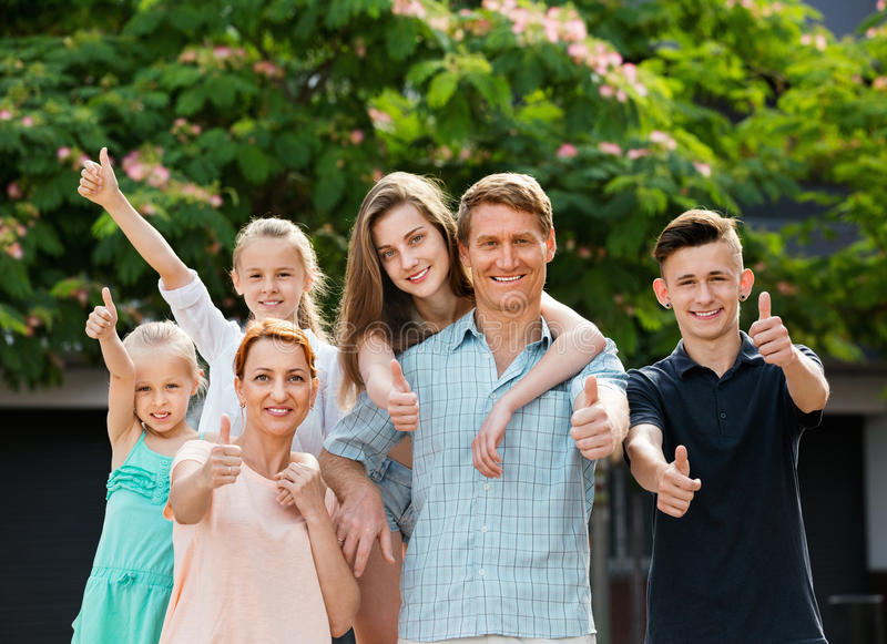 Portrait of large family of six standing and holding thumbs up. Portrait of happy large family of six standing and holding thumbs up together outdoors royalty free stock images