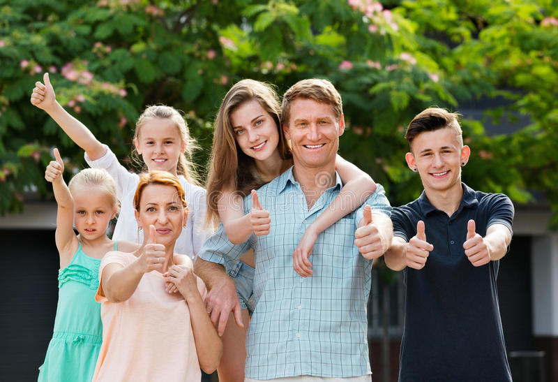 Portrait of large family of six standing and holding thumbs up stock photo