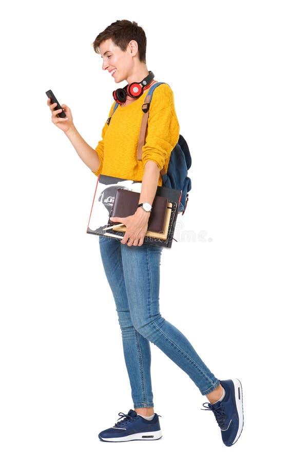Portrait latéral de jeune femme heureuse marchant avec le sac, livres et regardant le téléphone portable photos libres de droits