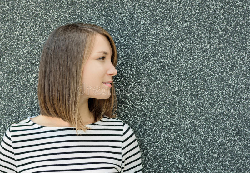 Portrait latéral de profil de jeune femme sur le fond gris de mur photographie stock libre de droits