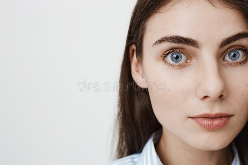 Portrait latéral en gros plan de l'étudiant assez européen doux regardant l'appareil-photo tout en se tenant sur le fond gris Fem images stock
