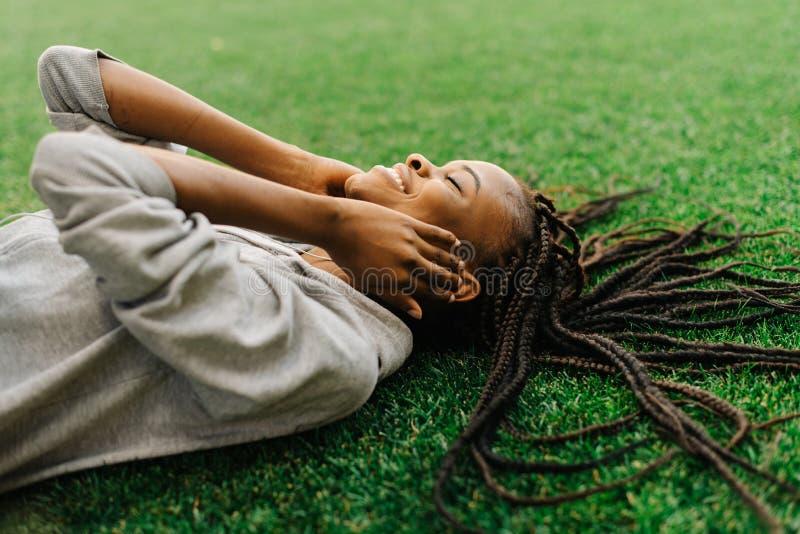 Portrait latéral en gros plan de la fille afro-américaine de sourire de charme appréciant la musique dans les écouteurs tout en s image stock