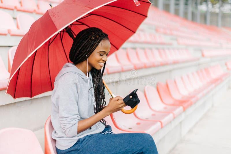 Portrait latéral en gros plan du service de mini-messages afro-américain joyeux de fille par l'intermédiaire du téléphone portabl image libre de droits