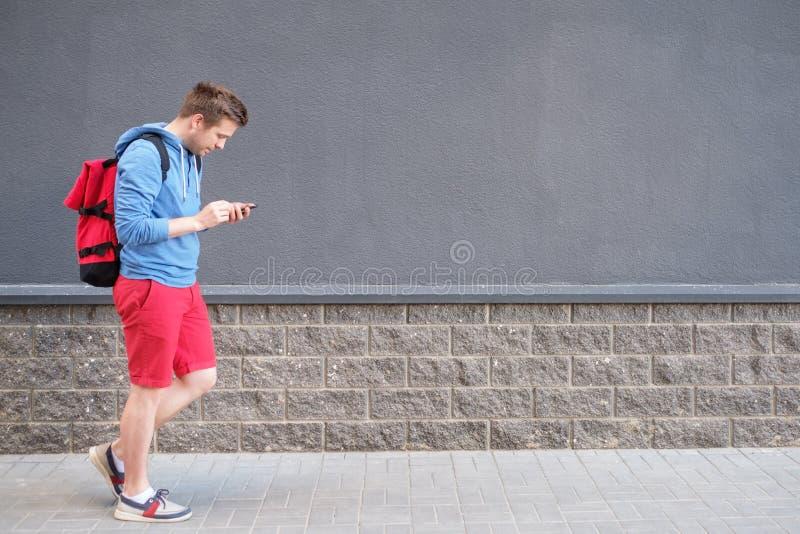 Portrait latéral intégral d'homme de sourire marchant sur le fond du mur noir photo stock