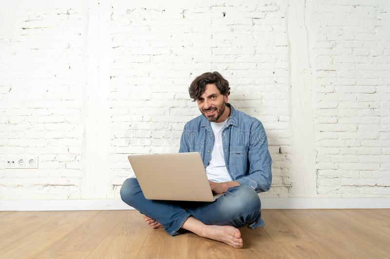 Freelance hipster working from home on a laptop with white brick wall background. stock image