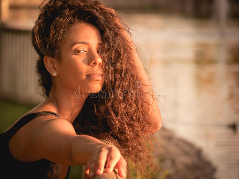 Portrait of Latina woman with her hair over her face. Warm portrait of Latina woman with her hair over her face stock image