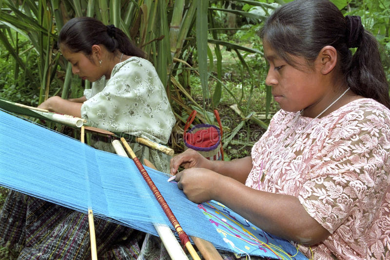 Portrait latino Indian women weaving on hand loom. Guatemala, village Parachoch [near Coban] Pokomchi Maya Indian young women during the weave work. Closeup of stock photography