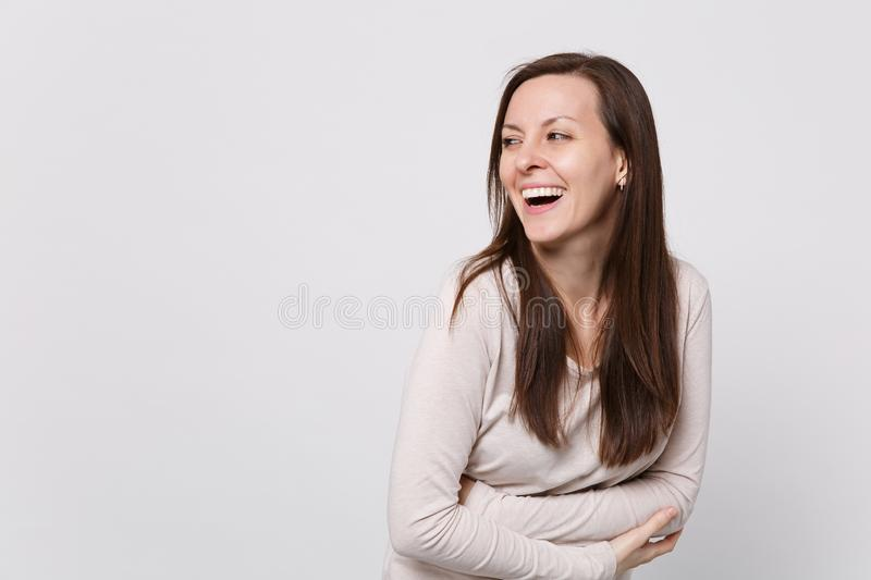 Portrait of laughing cheerful young woman in light clothes looking aside, holding hands folded on white stock photos