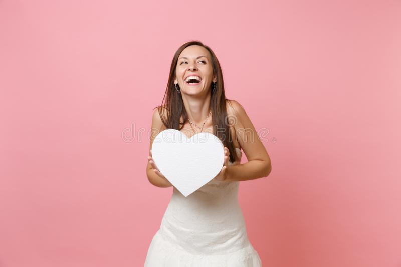 Portrait of laughing happy bride woman in beautiful white wedding dress standing holding white heart with copy space stock photos