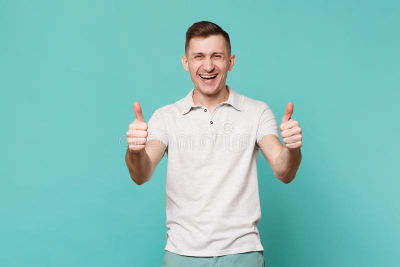 Portrait of laughing happy young man in casual clothes standing, showing thumbs up isolated on blue turquoise wall stock photography