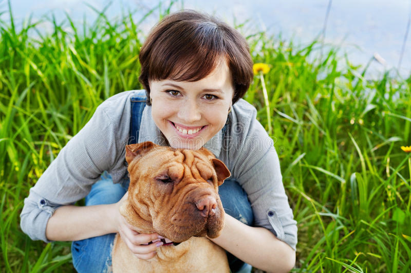 Portrait of laughing happy young woman in denim overalls hugging her red cute dog Shar Pei in the green grass in sunny day. True friends forever, people pets stock photo