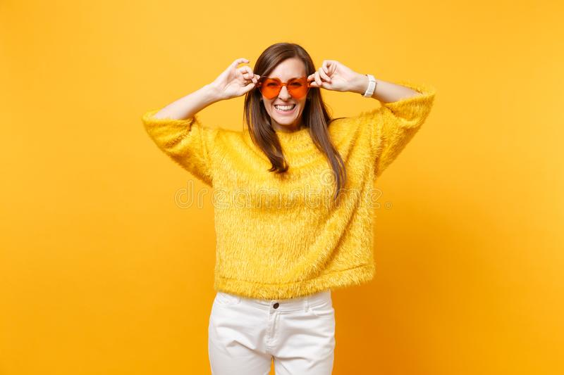 Portrait of laughing happy young woman in fur sweater, white pants holding heart orange eyeglasses isolated on bright royalty free stock images