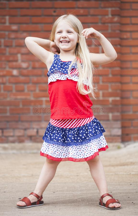 Portrait of laughing little girl touching hair outdoors royalty free stock image