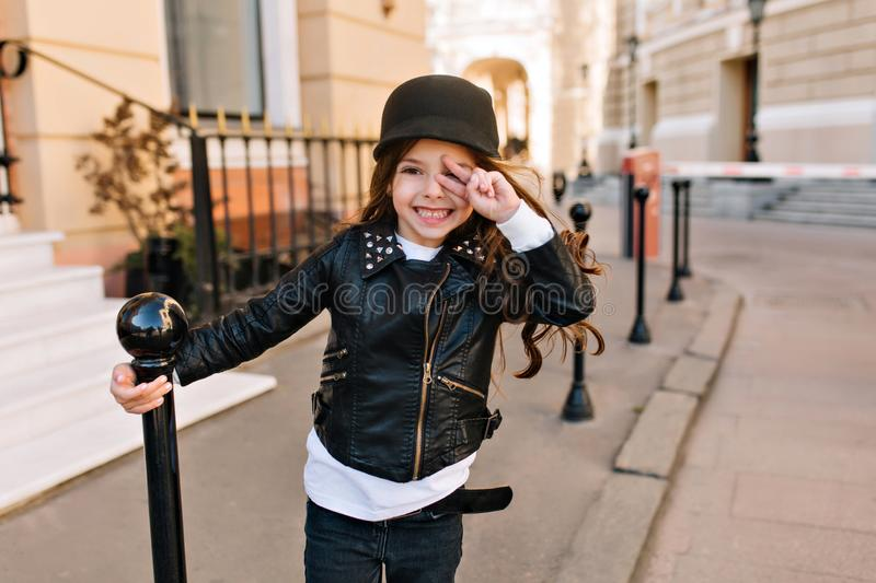 Portrait of laughing little girl in trendy black jacket and white shirt waiting friends on the street. Cute long-haired royalty free stock images